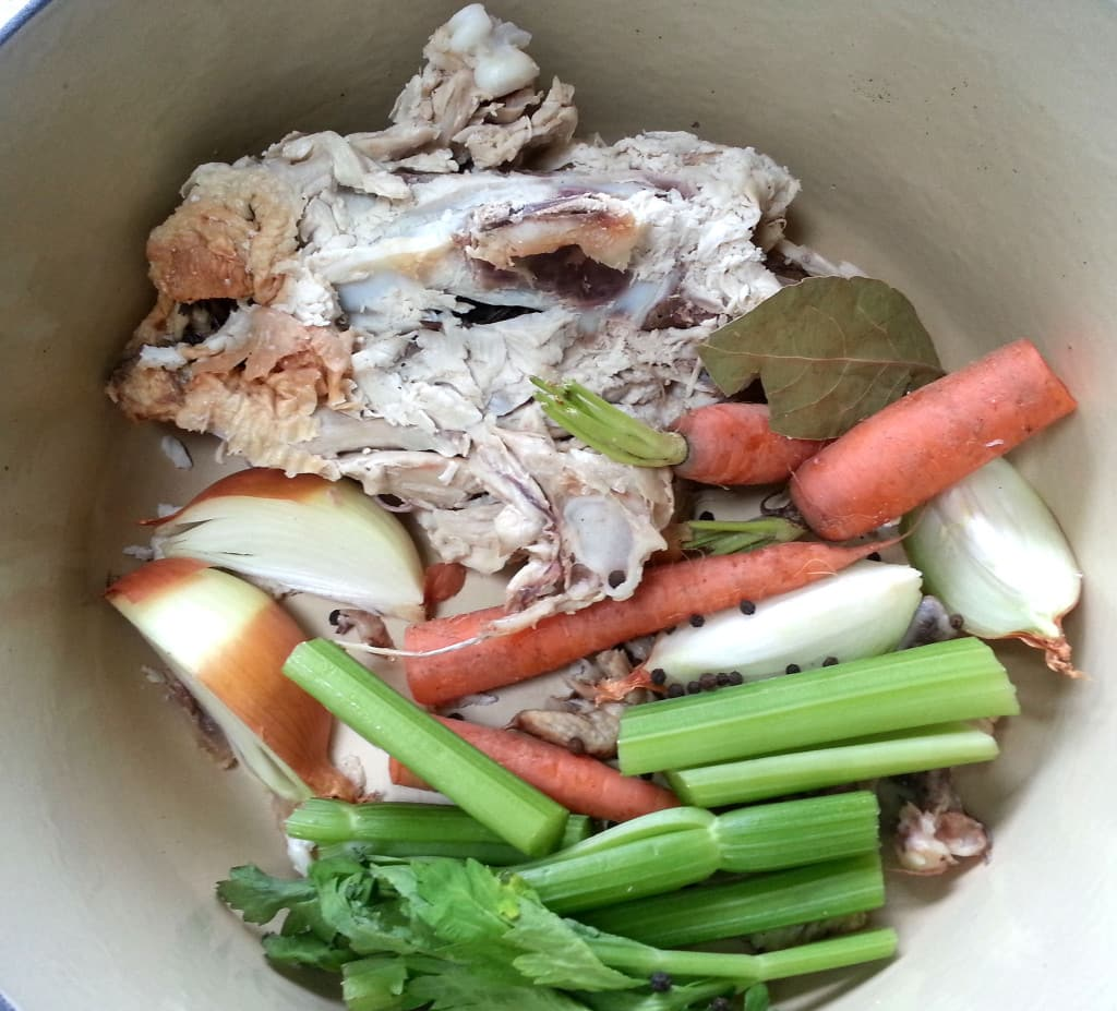 Add the unpeeled vegetables and aromatics to the pot.