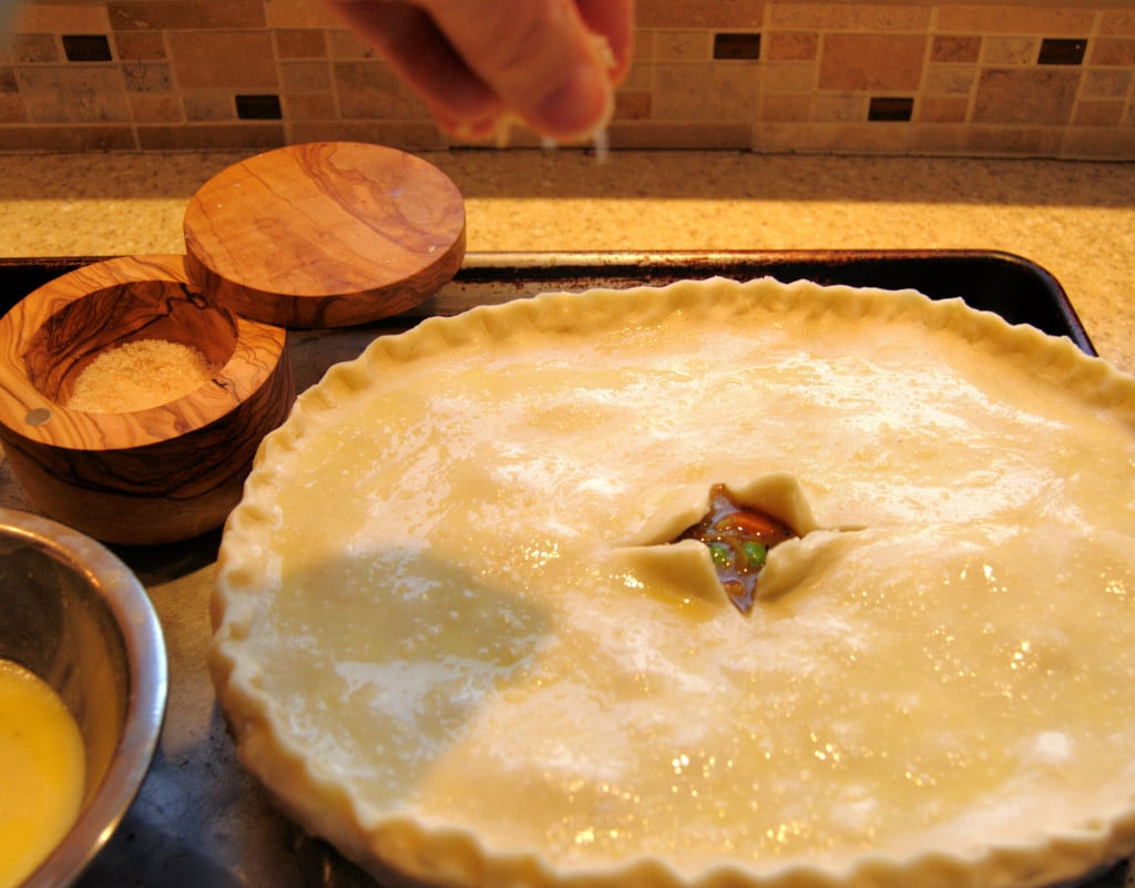 Brush the rim of the dish before placing the crust on top. This will keep the crust from pulling away from the pan.