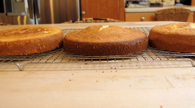 Three cakes on a cooling rack with kitchen in the background.