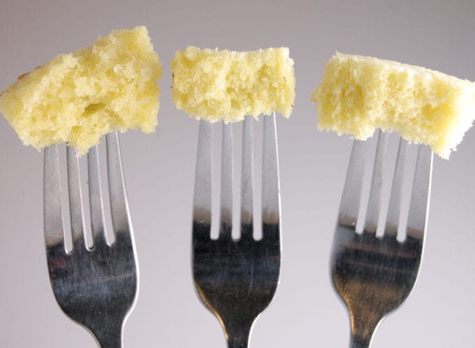 Closeup of three forks with a bite of cake at the end of each fork. Gray background