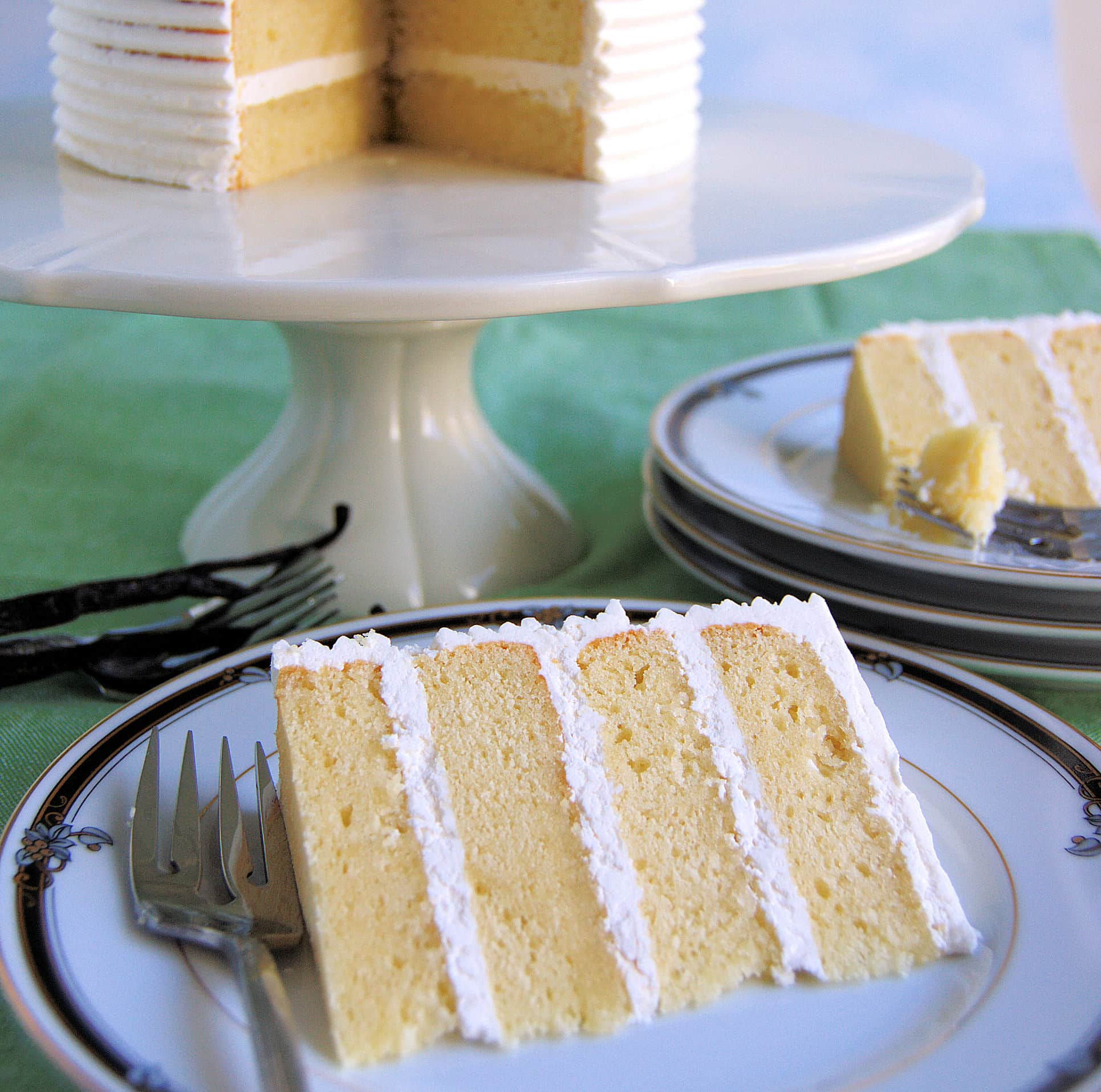 a 34 layer slice of vanilla cake with a fork on a white plate.