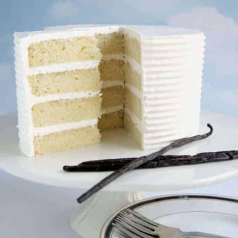 A four layer Vanilla cake on a white cake stand.