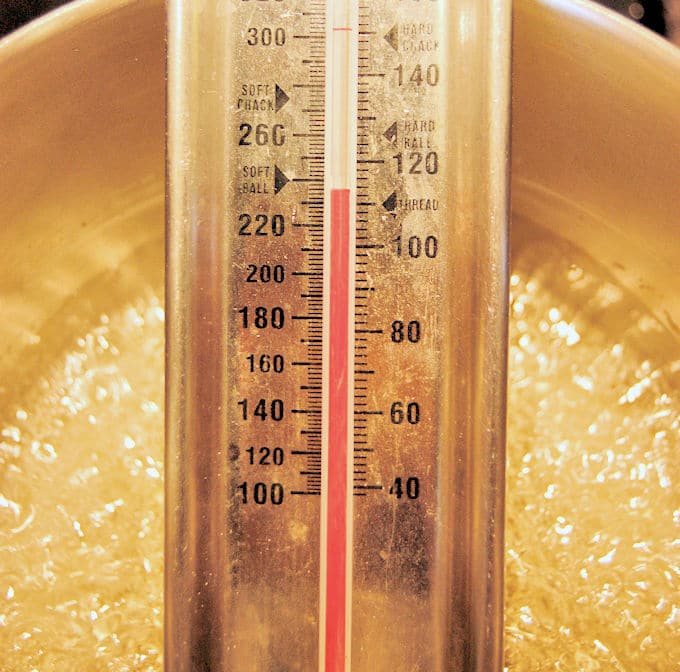 a closeup of a pan of boiling sugar syrup with a candy thermometer showing the temperature of 235 degrees F.