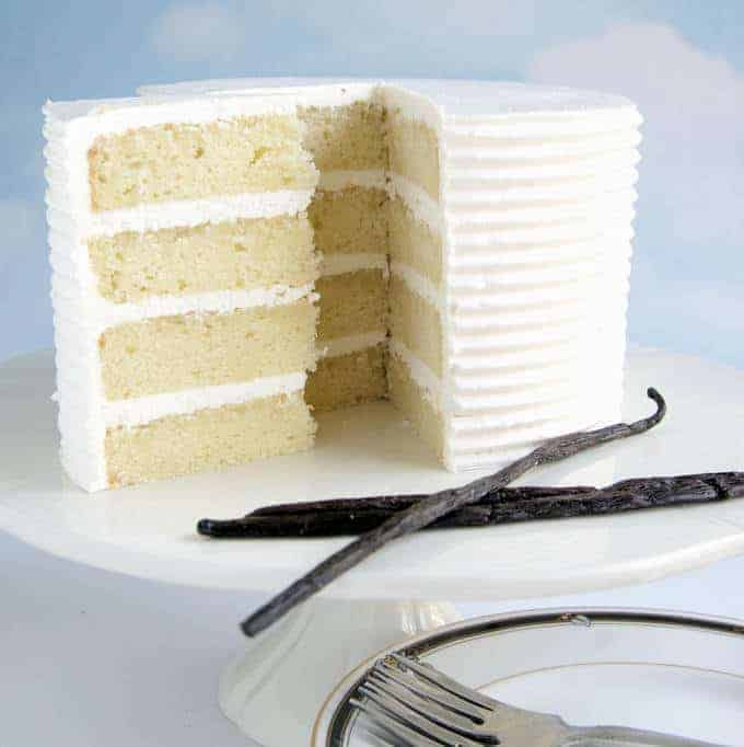 a four layer vanilla cake on a white cake stand