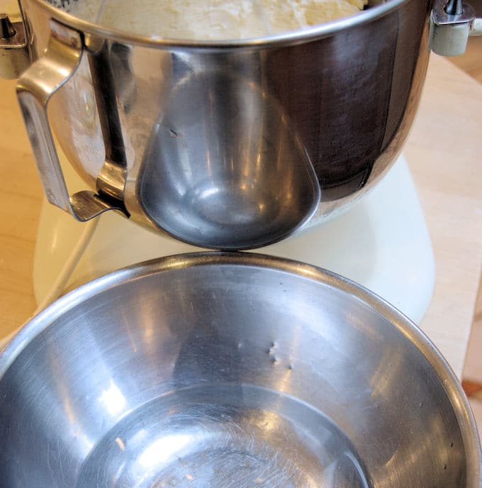 A stand mixer bowl full of buttercream with a smaller bowl of warm water underneath