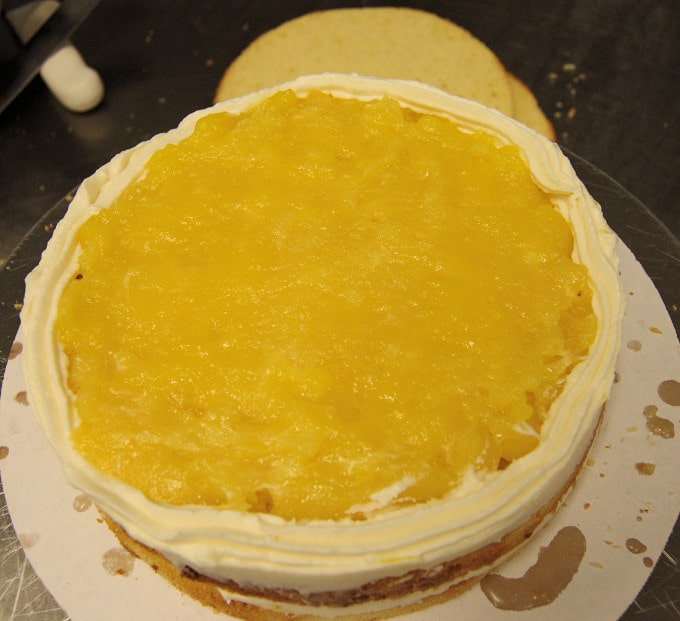 a layer of passion fruit curd on a cake