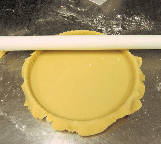 Push the dough into the fluted edges then use the rolling pin to cut off the excess dough