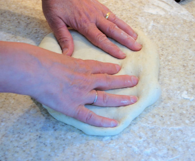 To form the pizza shape, gently push the dough into a flattened disc
