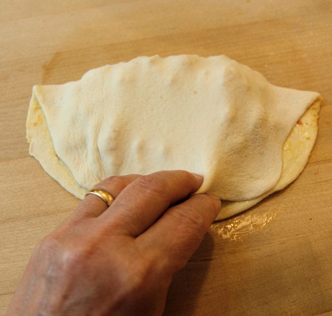 Fold the top 1/2 of the dough over the filling bring it just short of the bottom of the dough. Fold the bottom over the top to form a tight seal.