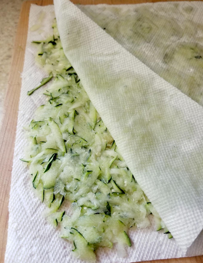 shredded zucchini layered between paper towels