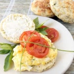 a zucchini biscuit on a plate with scrambled eggs and tomatoes
