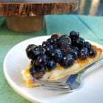 a slice of blueberry cheesecake tart on a white plate