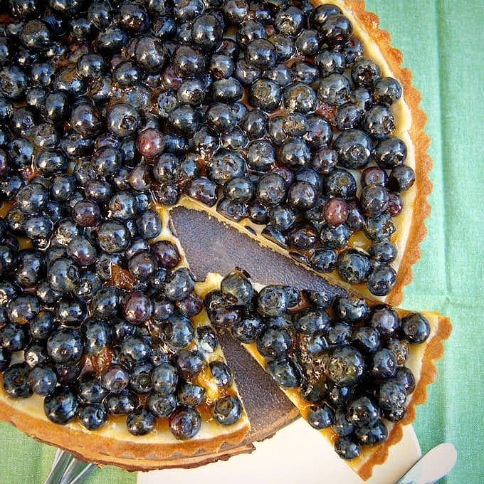 a sliced blueberry cheesecake tart