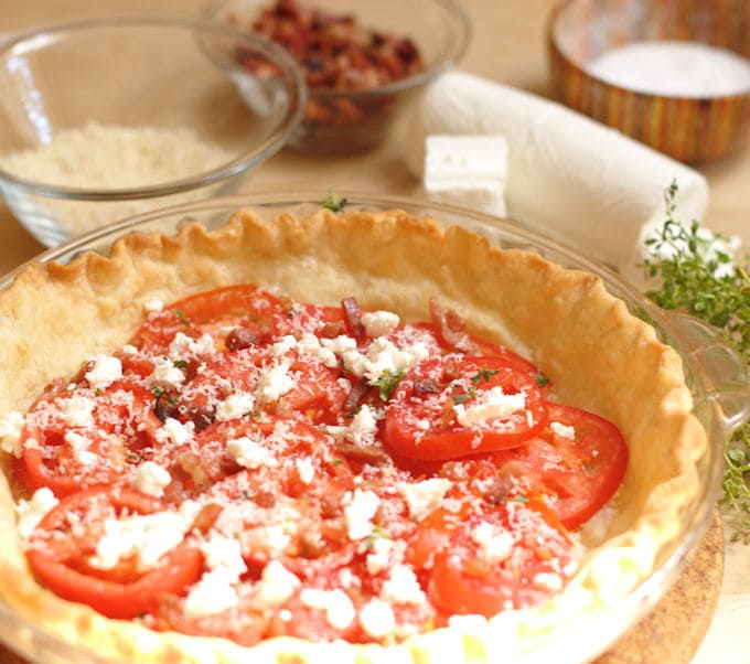 a pie shell filled with heirloom tomatoes and cheese ready for more layering