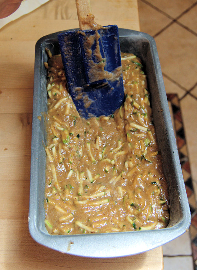 spreading zucchini bread batter into a loaf pan