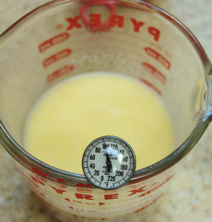 a measuring cup with milk and thermometer reads 100 degrees