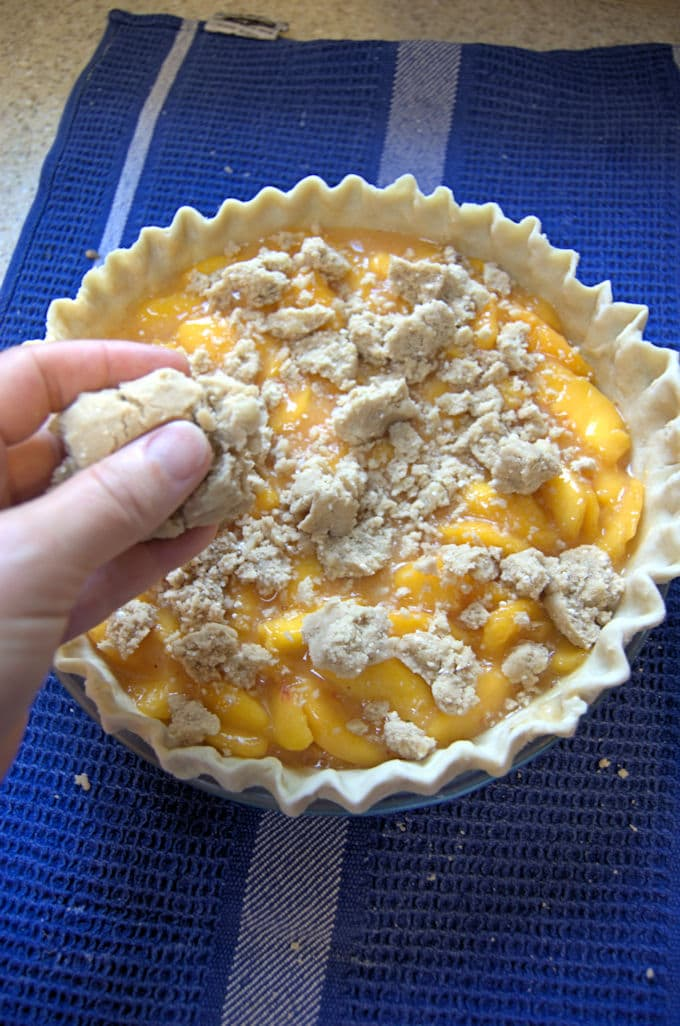 crumbling topping on a peach pie