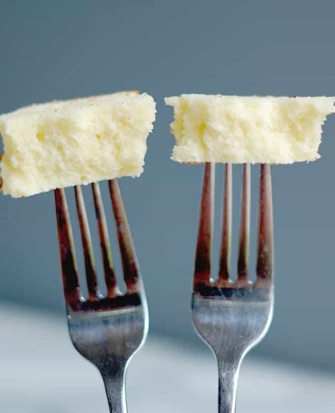 Two forks each with a bite of cake at the end against a gray background