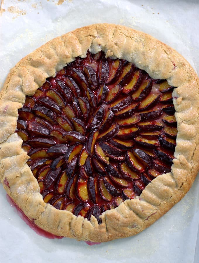 plum galette with a walnut crust on a baking pan