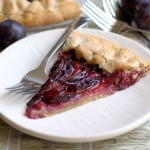 a slice of rustic plum tart with walnut crust
