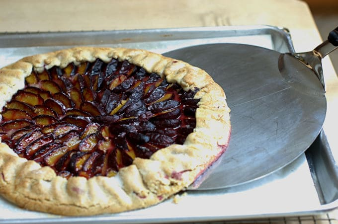 a plum tart sliding off a pan