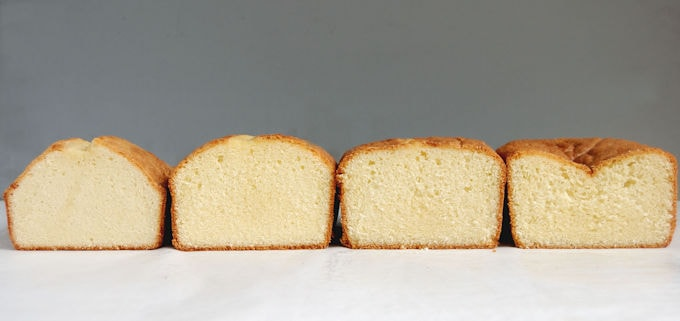 Four pound cakes standing side by side on a white surface with a gray background