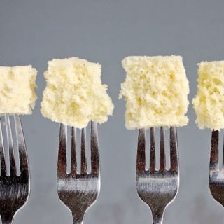 Four forks with pieces of cake at the end of each fork. Gray background.