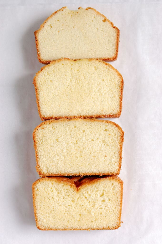 Four slices of pound cake lined up on a white background