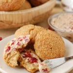 a plate of gingerbread scones with cranberry maple butter spread on one scone