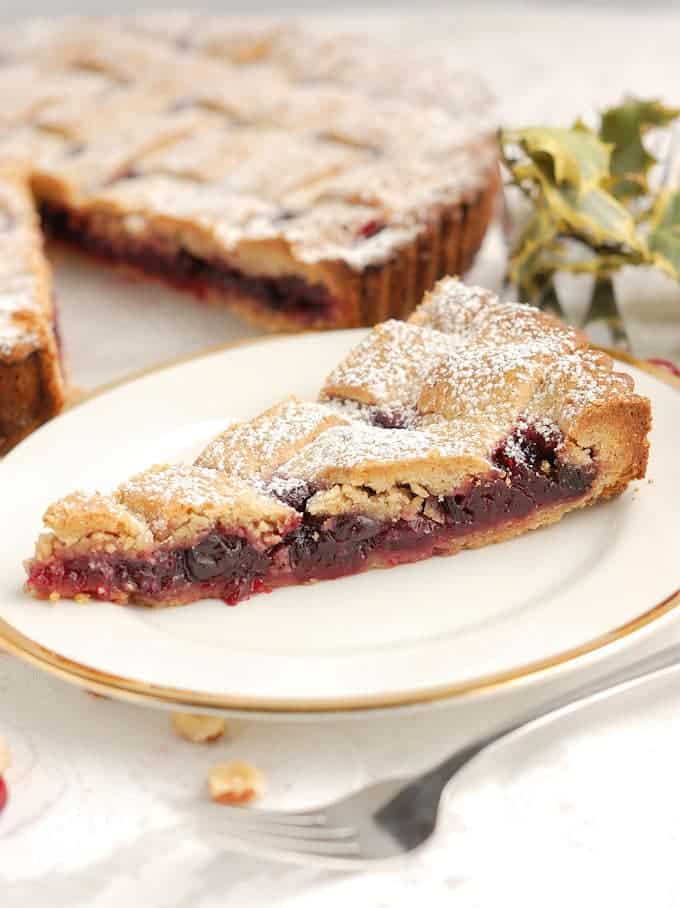 a slice of cranberry linzer tart on a plate