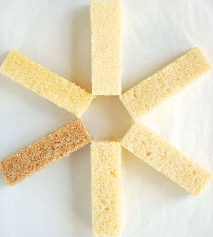 Five pieces of cake arranged in pinwheel pattern on a white surface