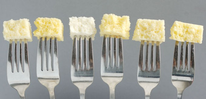 Six forks each with a bite of cake at the end against a gray background. Shows how in Cake batter eggs make a huge difference