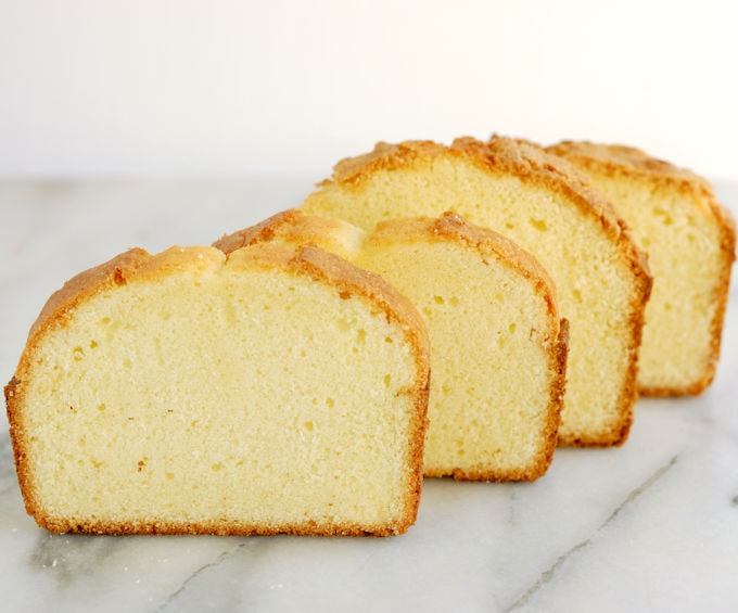 Four slices of pound cake standing in a row on a marble slab. cake batter sugar amounts.