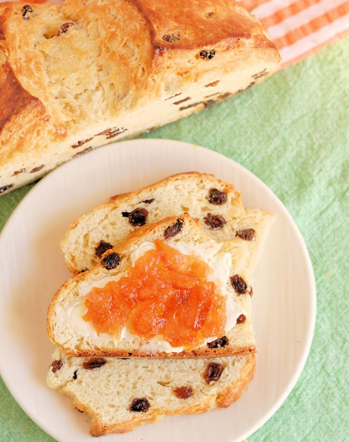 slices of irish soda bread with butter and orange marmalade on a white plate