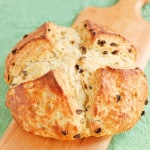 A loaf of Irish soda bread with raisins is set on a wooden cutting board with a green background.