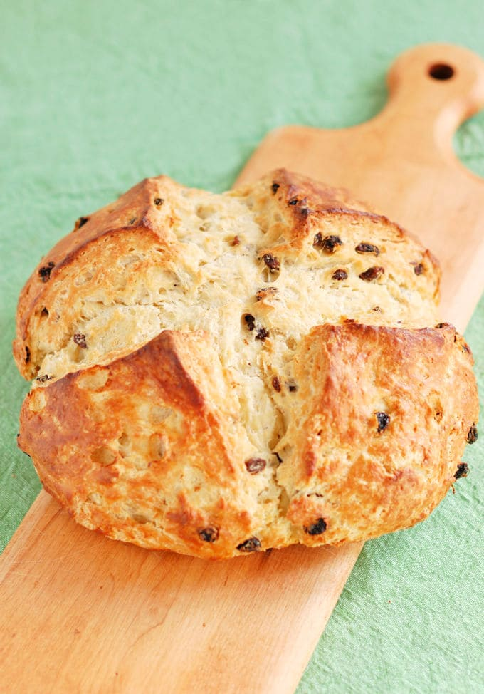 a loaf of Irish soda bread with raisins on a wooden board with a green background
