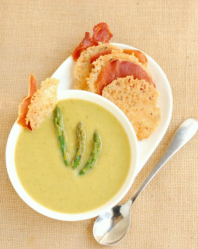 a bowl of asparagus soup with parmesan and prosciutto crisps