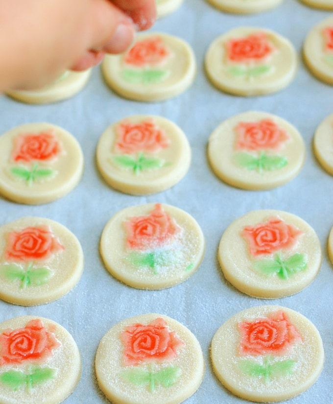 rose shortbread cookies getting sprinkled with sugar