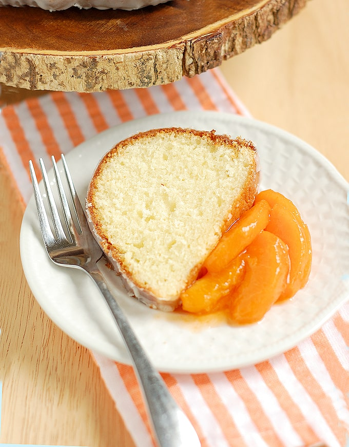 a slice of buttermilk bundt cake on a plate with sliced apricots