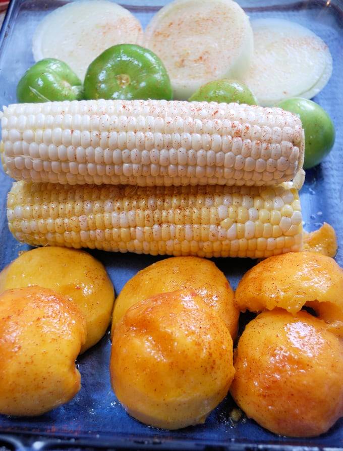 peaches, corn, onions and tomatillos in a baking dish