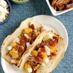 a plate of pulled pork tacos with peach salsa