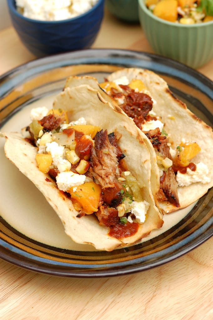 two pulled pork tacos with grilled peach salsa