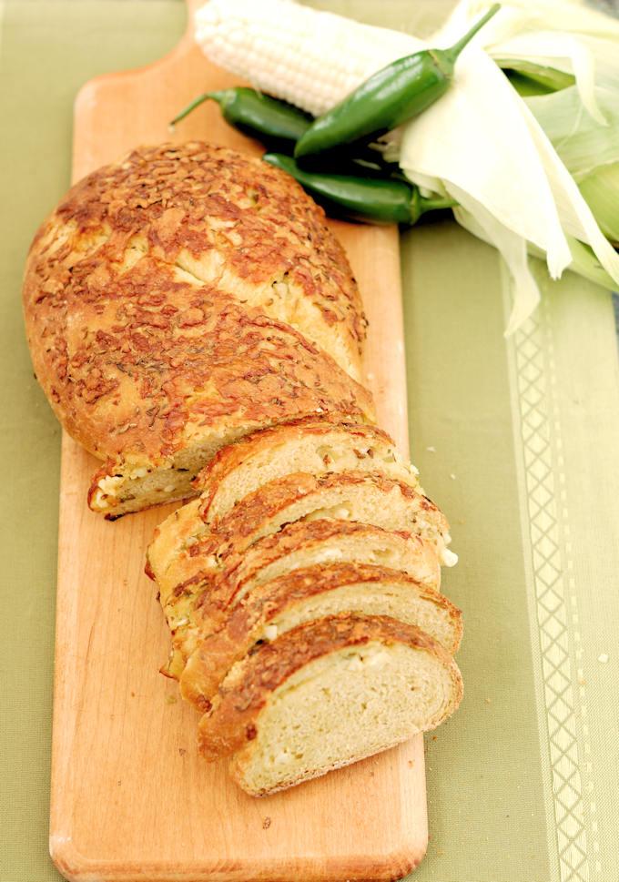 a sliced loaf of sourdough cornbread on a cutting board