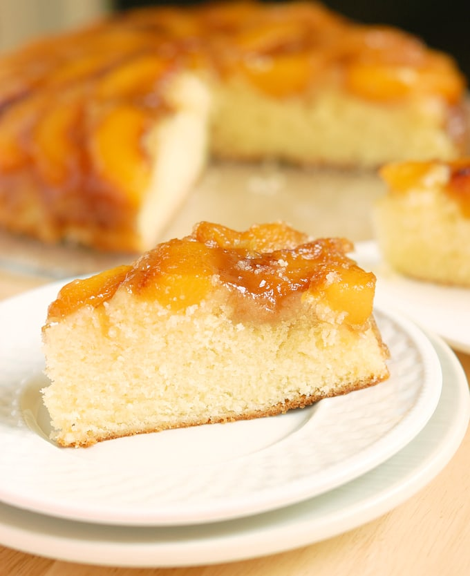 a slice of peach upside down cake on a white plate
