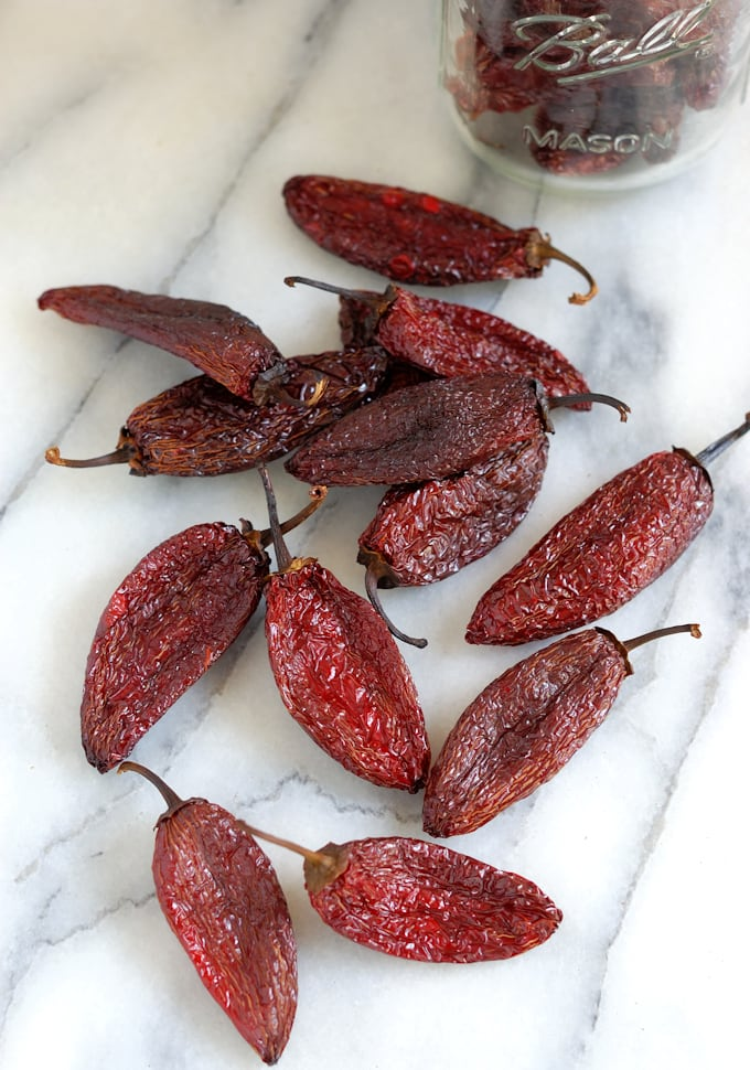 dried chipotle peppers on a marble surface