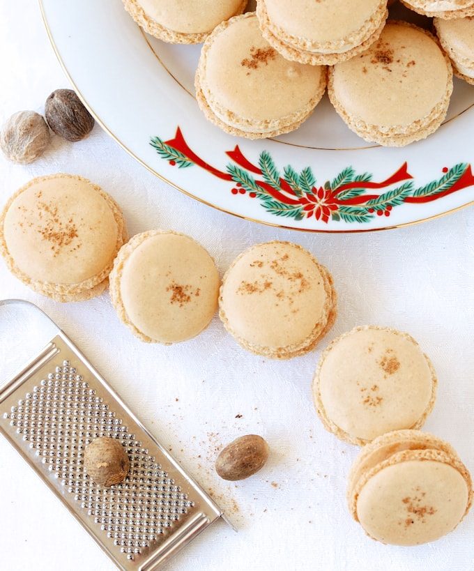 a plate with eggnog macarons plus some on a table with nutmeg and grater