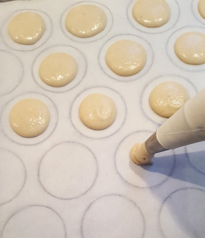 piping french macarons on a sheet pan