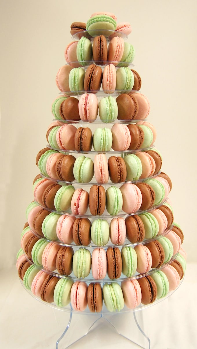 a french macaron display tree with brown pink and green cookies