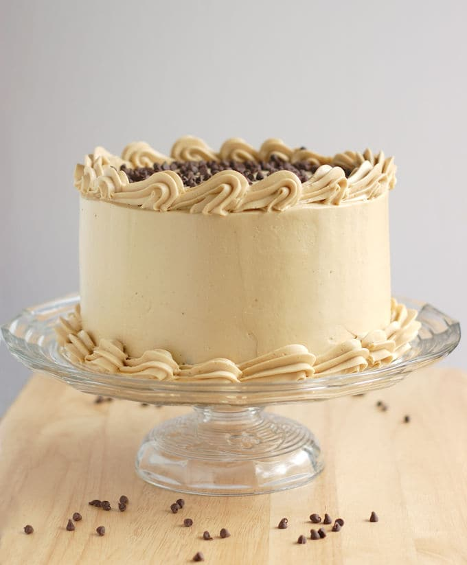 a chocolate chip cookie cake iced with Italian Meringue brown sugar buttercream on a glass cake stand