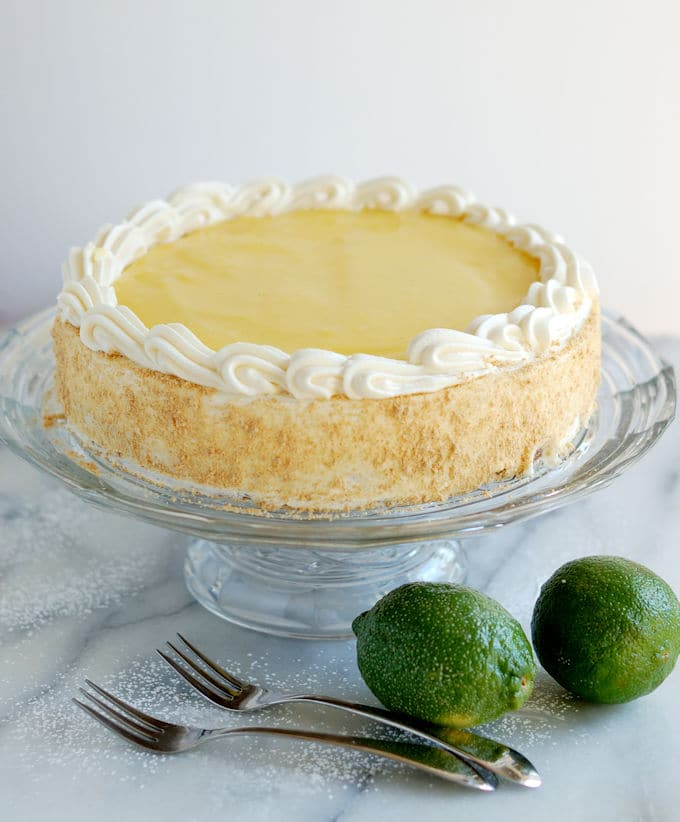 a lime layered cheesecake on a glass cake stand